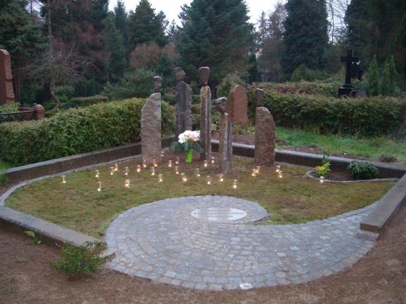 5 stilisierte Kinder aus Granit und eine spiralförmige Pflasterung setzen die Akzente der mit Rasen belegten Grabstelle.