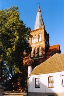 Rechts im Vordergrund die Pilgerherberge. Links eine Linde. Im Hintergrund der Turm von St. Marien.